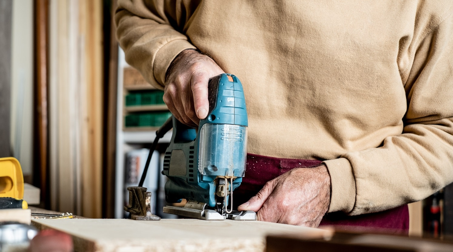 Carpenter's hands with electric jigsaw close-up. Work in a carpentry workshop. A man cuts plywood with an electric jigsaw. Electric tool for woodworking.