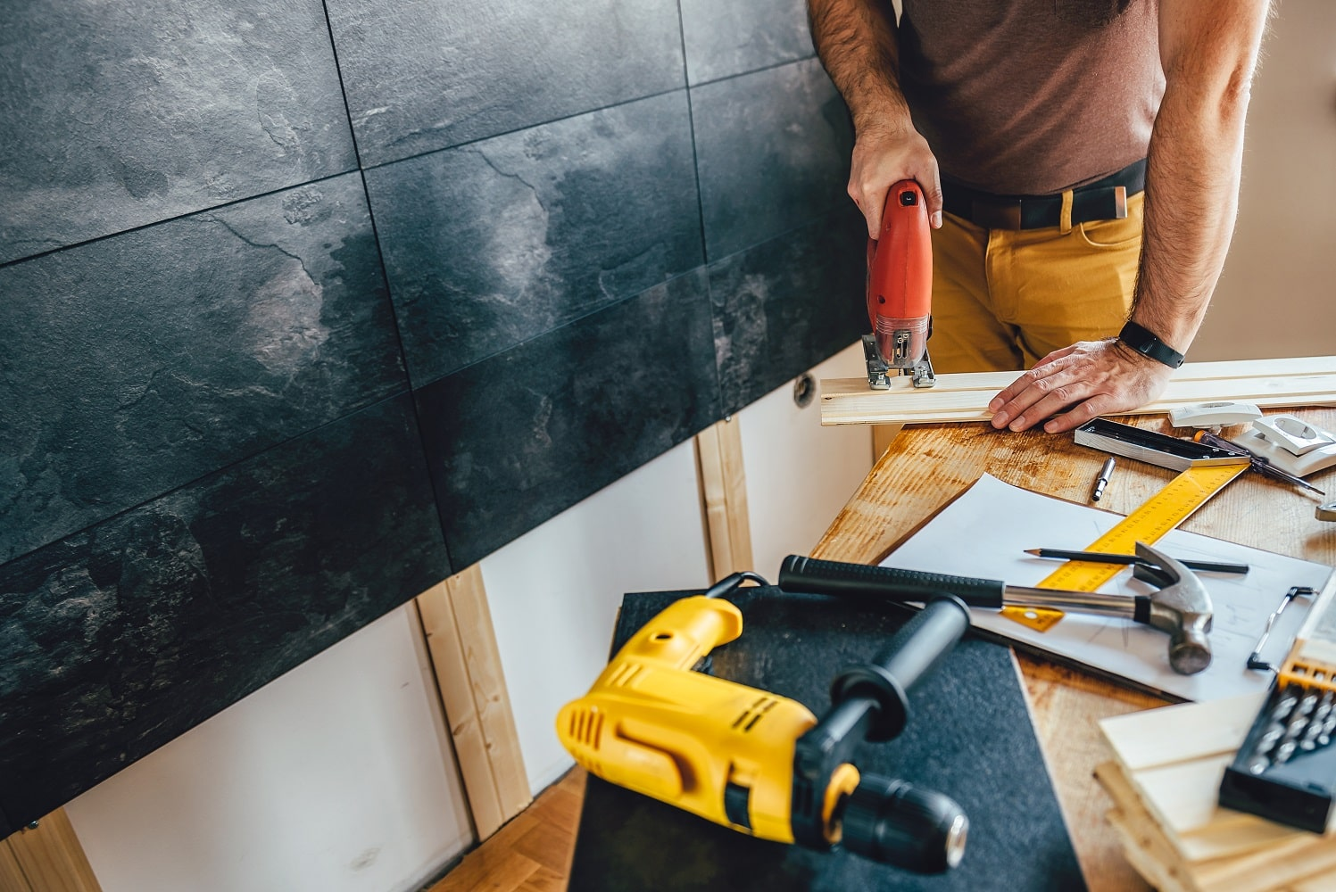 Man cutting piece of wood on the table with electric Jigsaw at home