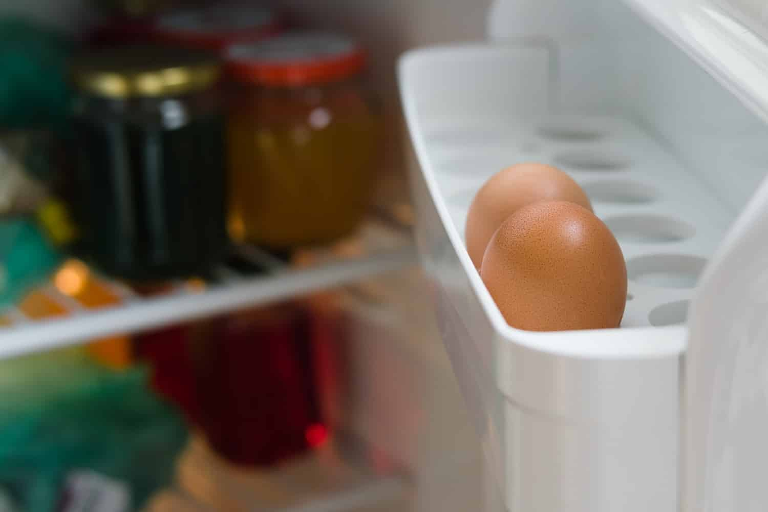 Two chicken eggs on a shelf of the refrigerator door close-up. Inside the refrigerator glass jars.
