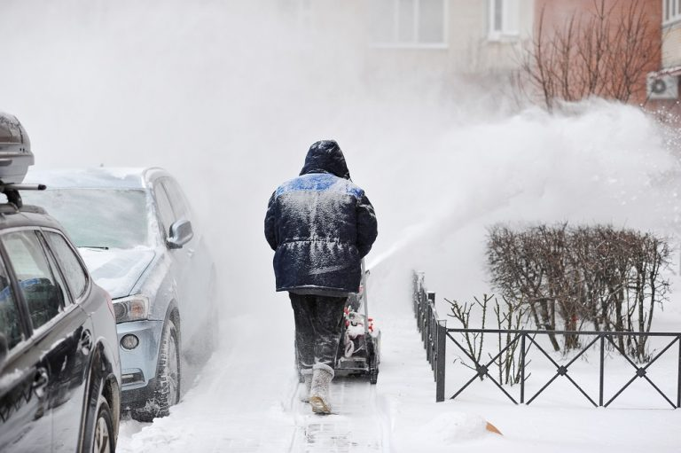 man removes snow in the yard of a multistory building with snow machines
