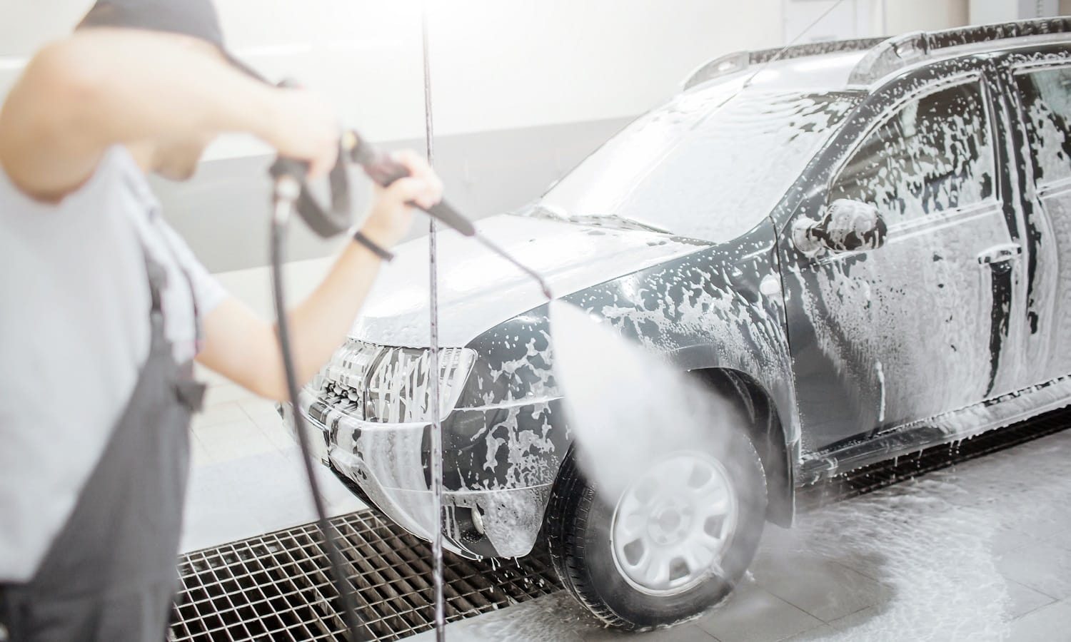 Another picture of man standing in room and washing car's wheel abd tire. He usies flexible hose with water for that. He is concentrated on process