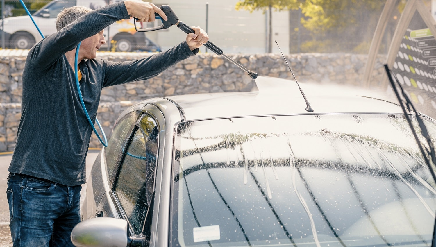 Man washing his car with using a high pressure water jet. man washing his car with compression water. Man washing his car in a self-service car wash station