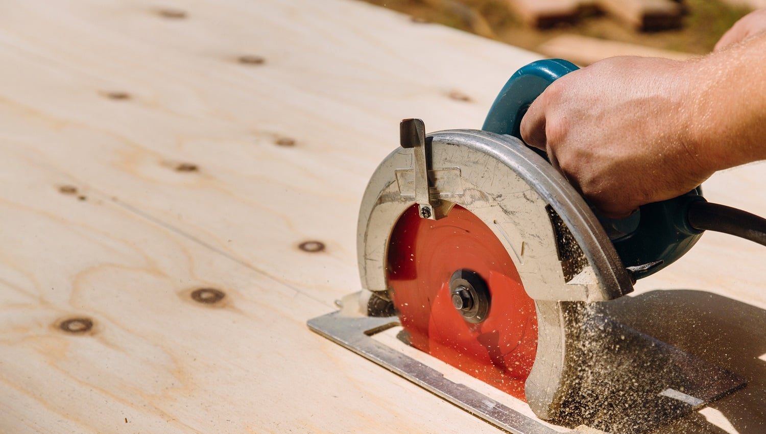 Handyman cutting plywood on hand held worm drive circular saw