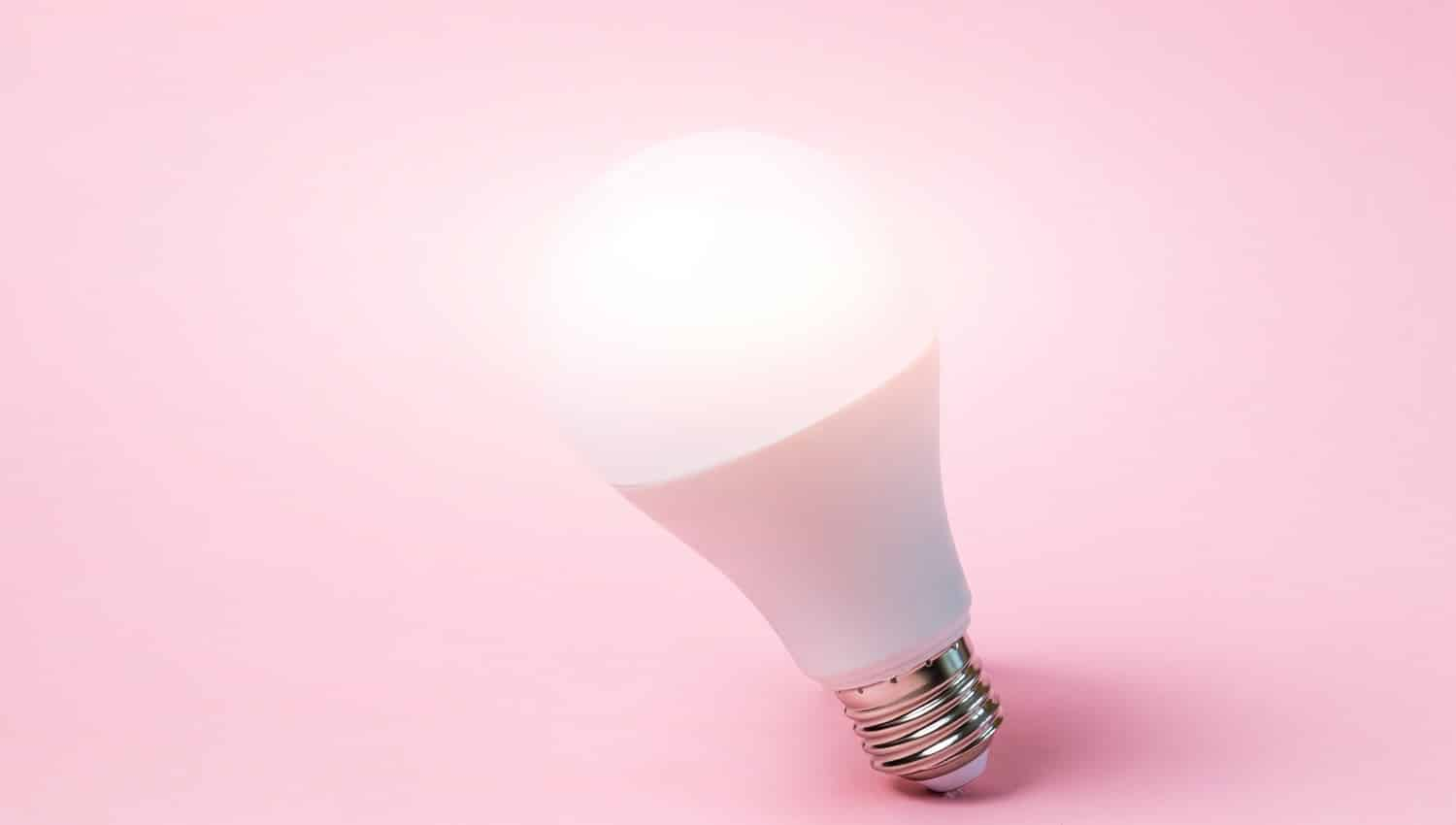 LED light bulb stands on a pastel pink background. Light from the lamp. Concept of idea. Minimalism, place for text.