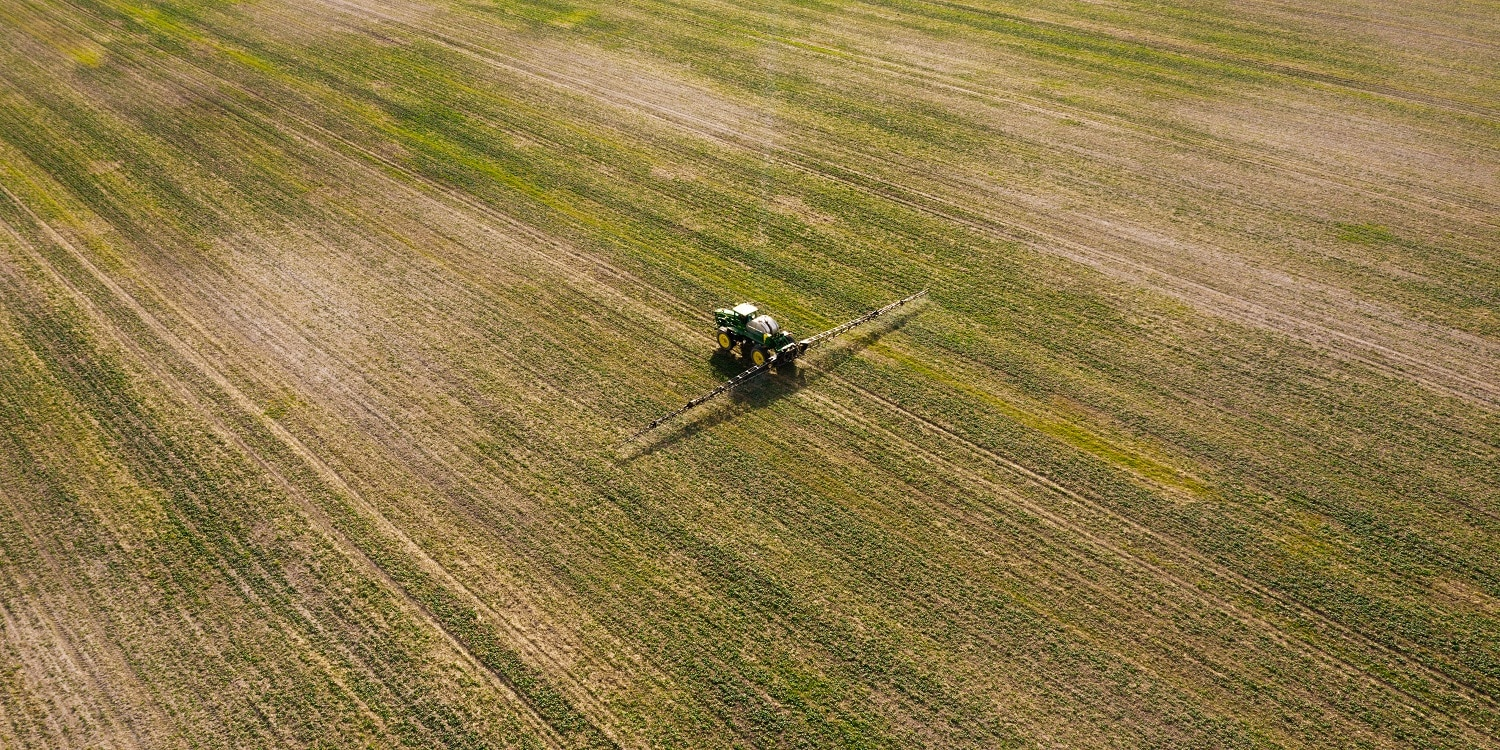 Aerial view of spraying machine working on the green field. Agriculture and farming concept.
