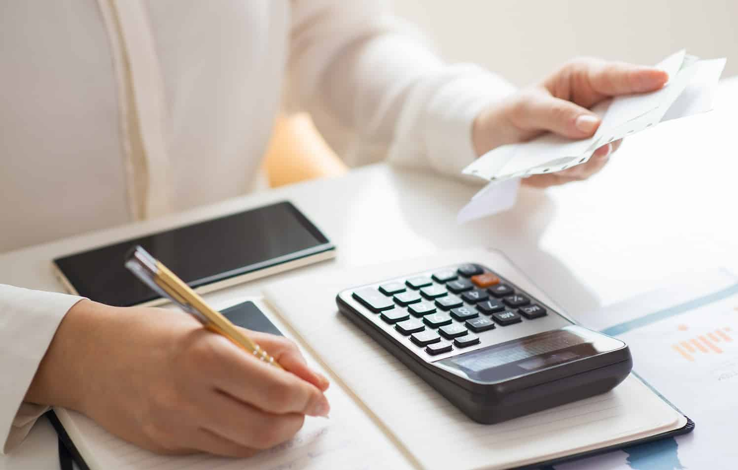 Closeup of person holding bills and calculating them. Notebook, calculator and smartphone lying on desk. Payment concept. Cropped view.