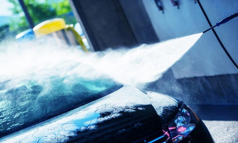 Hand Car Wash Cleaning. Bluish Color Grading. Cleaning Modern Compact Car.