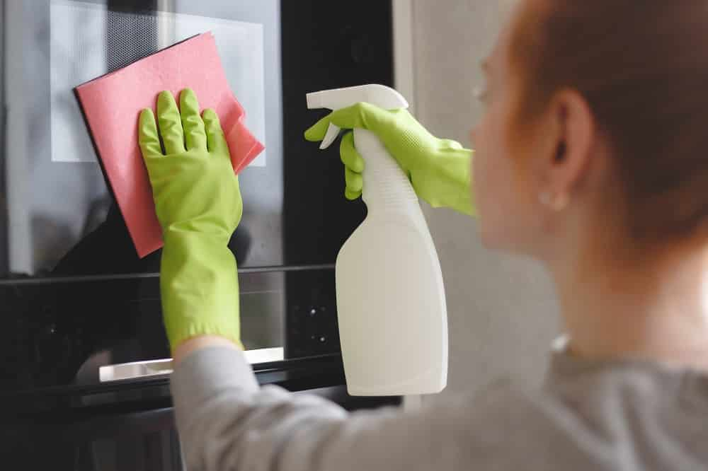 Woman cleaning oven and microwave with rag in kitchen, close up.