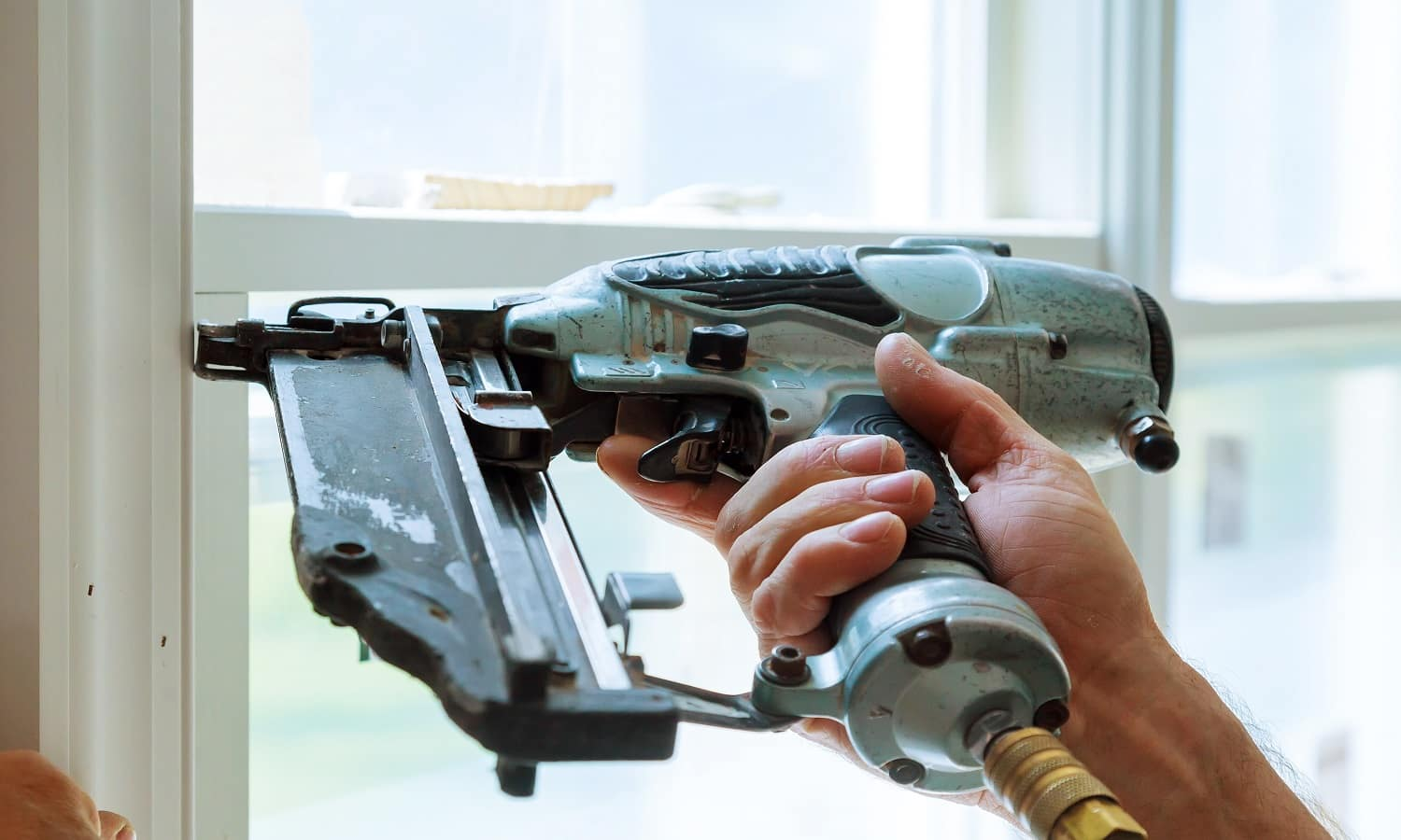 Carpenter brad using nail gun to moldings on windows, framing trim, with the warning label that all power tools have on them shown illustrating safety concept