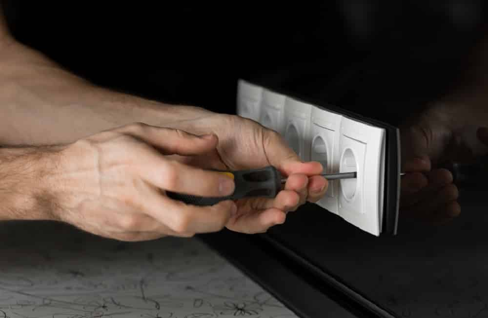 Close-up of an electrician's hand with a screwdriver disassembling a white electrical outlet on a black glass wall.