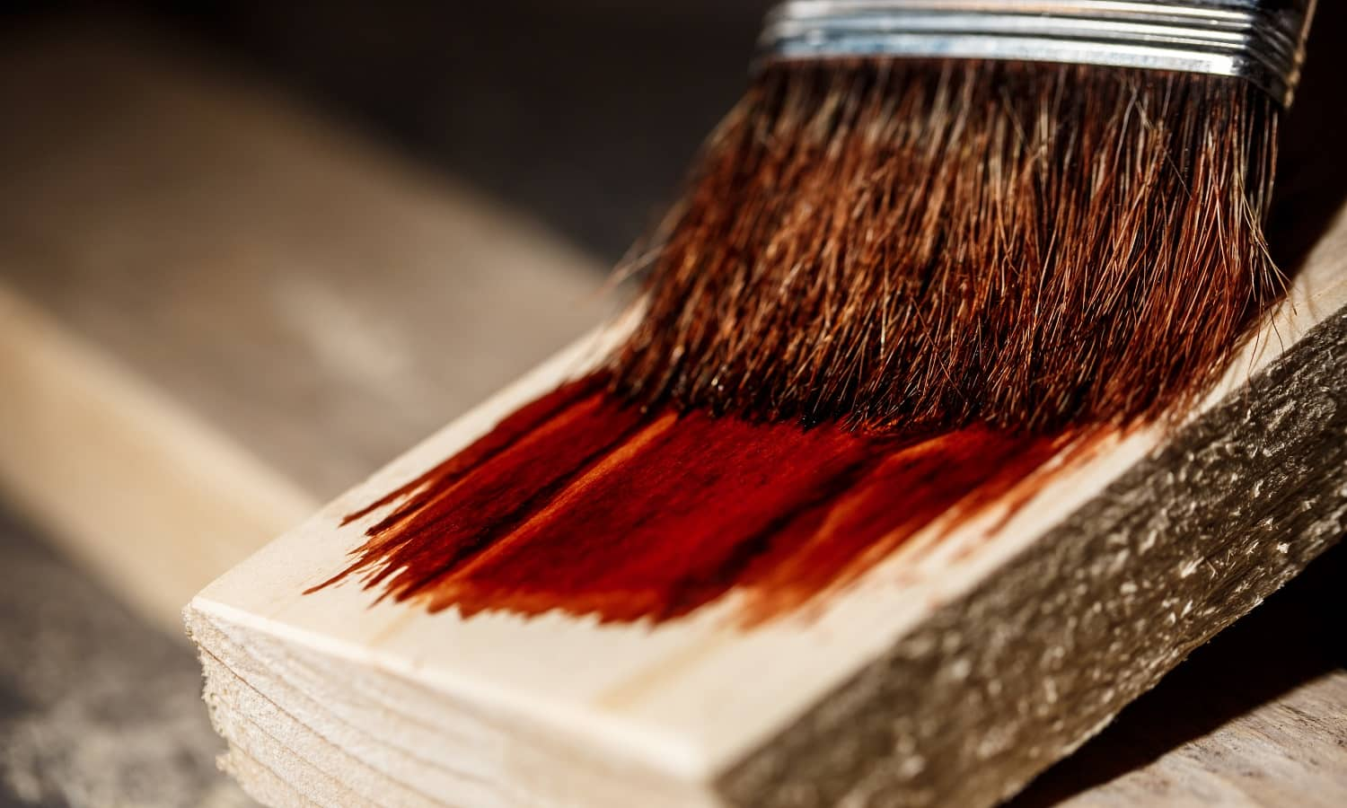 Close up photo of painting wood in brown color over dark background. Copy space.