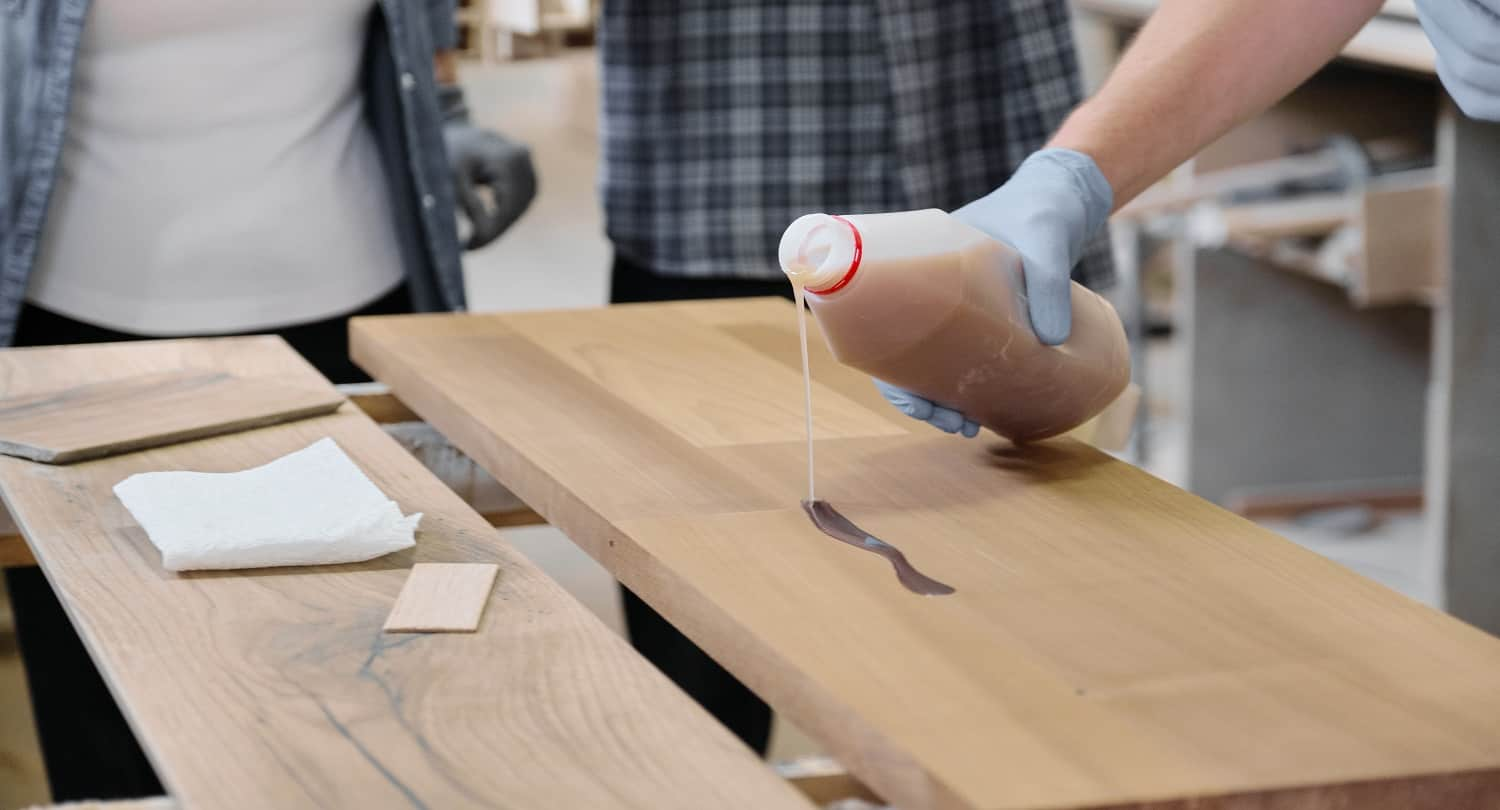Closeup of worker hand in protective gloves with finishing protective cover for wood, background carpentry furniture woodworking production