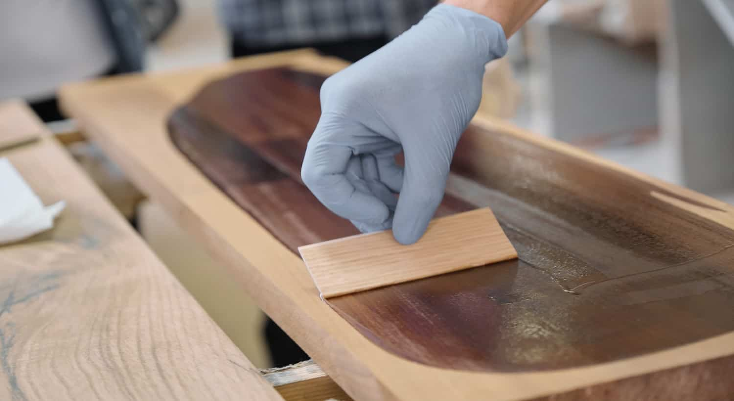 Closeup of workers hand covering wooden plank with finishing protective cover for wood, carpentry furniture woodworking production