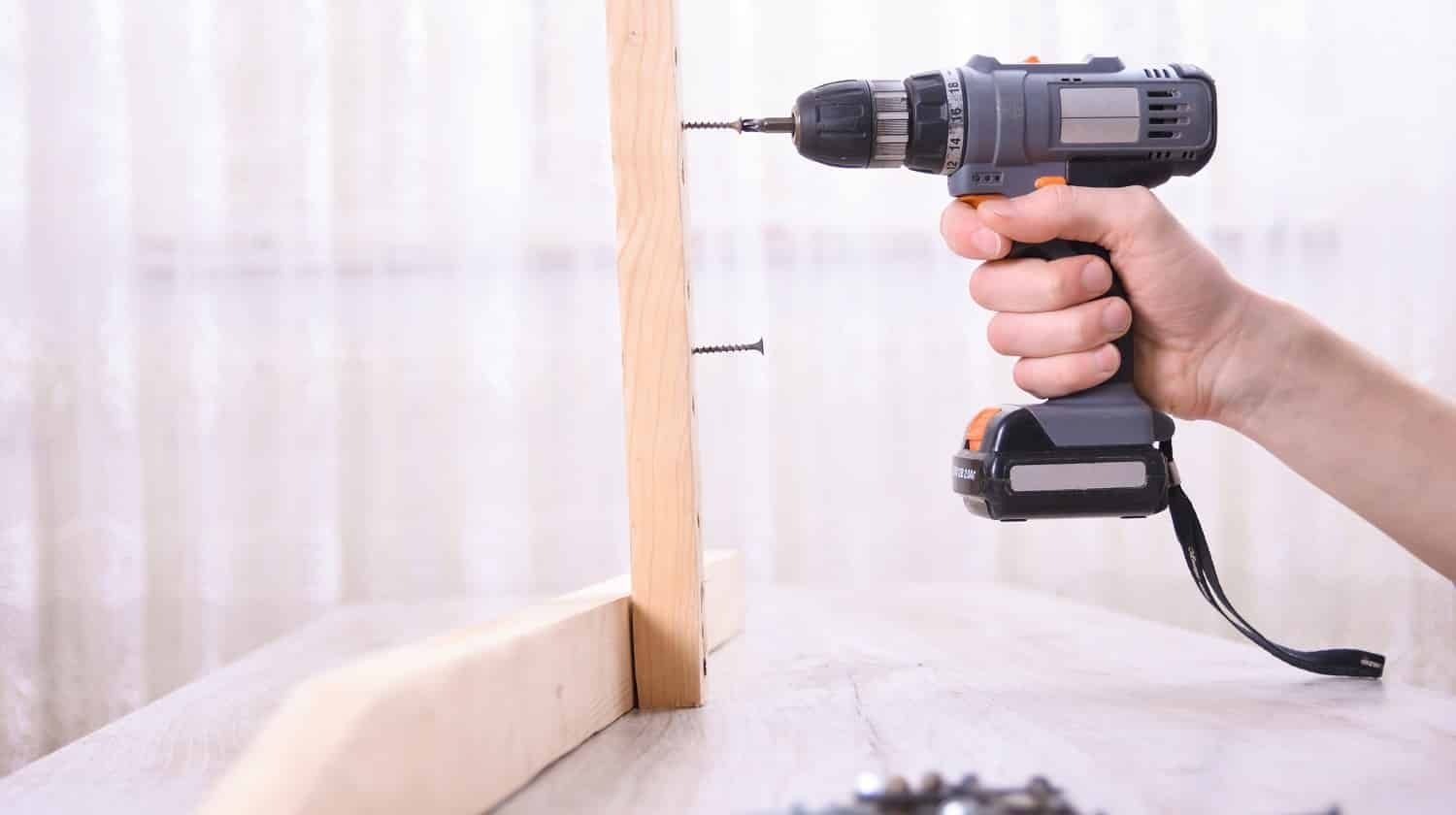 Man is working with furniture assembly using electric screwdriver in new house installation - technician onsite work using hand tools a concept