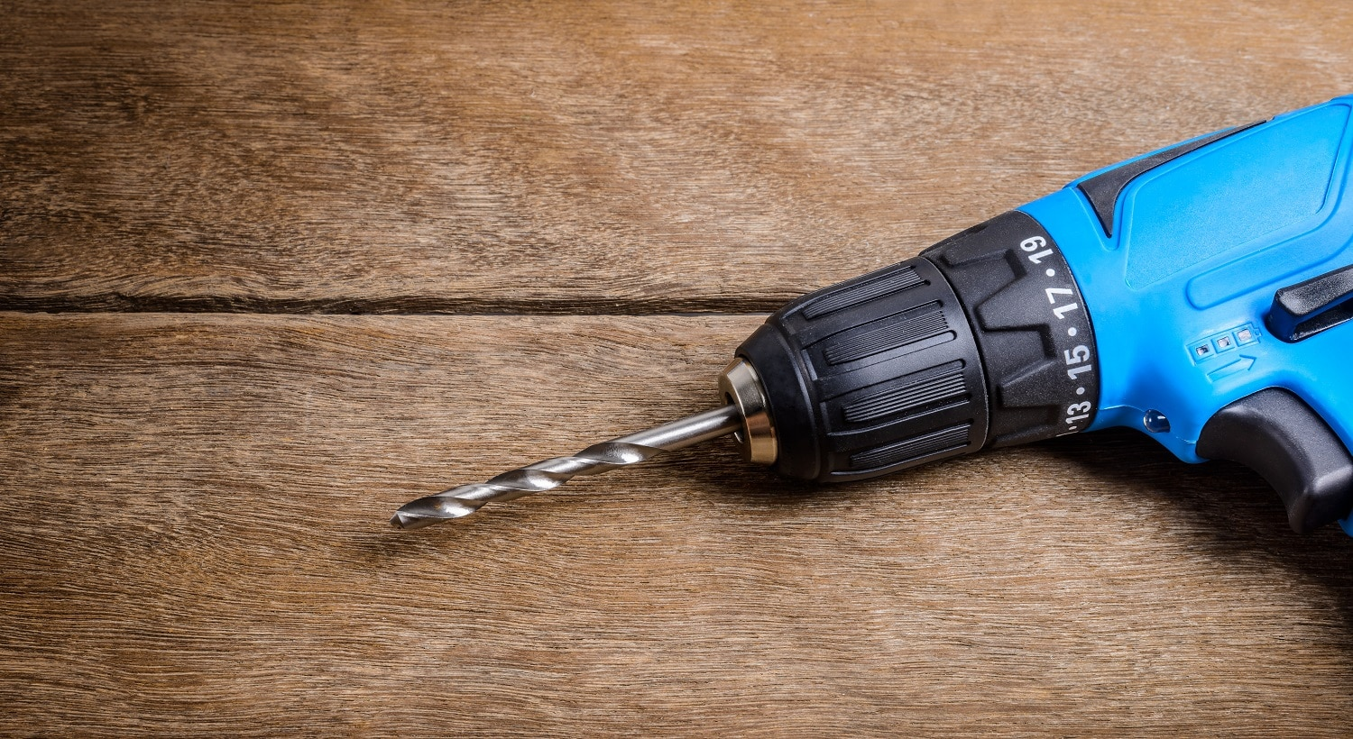 Close up Electric drill on wooden table background and copy space. Hammer drill or screwdriver, Electric cordless hand drill on wooden. maintenance home concept.