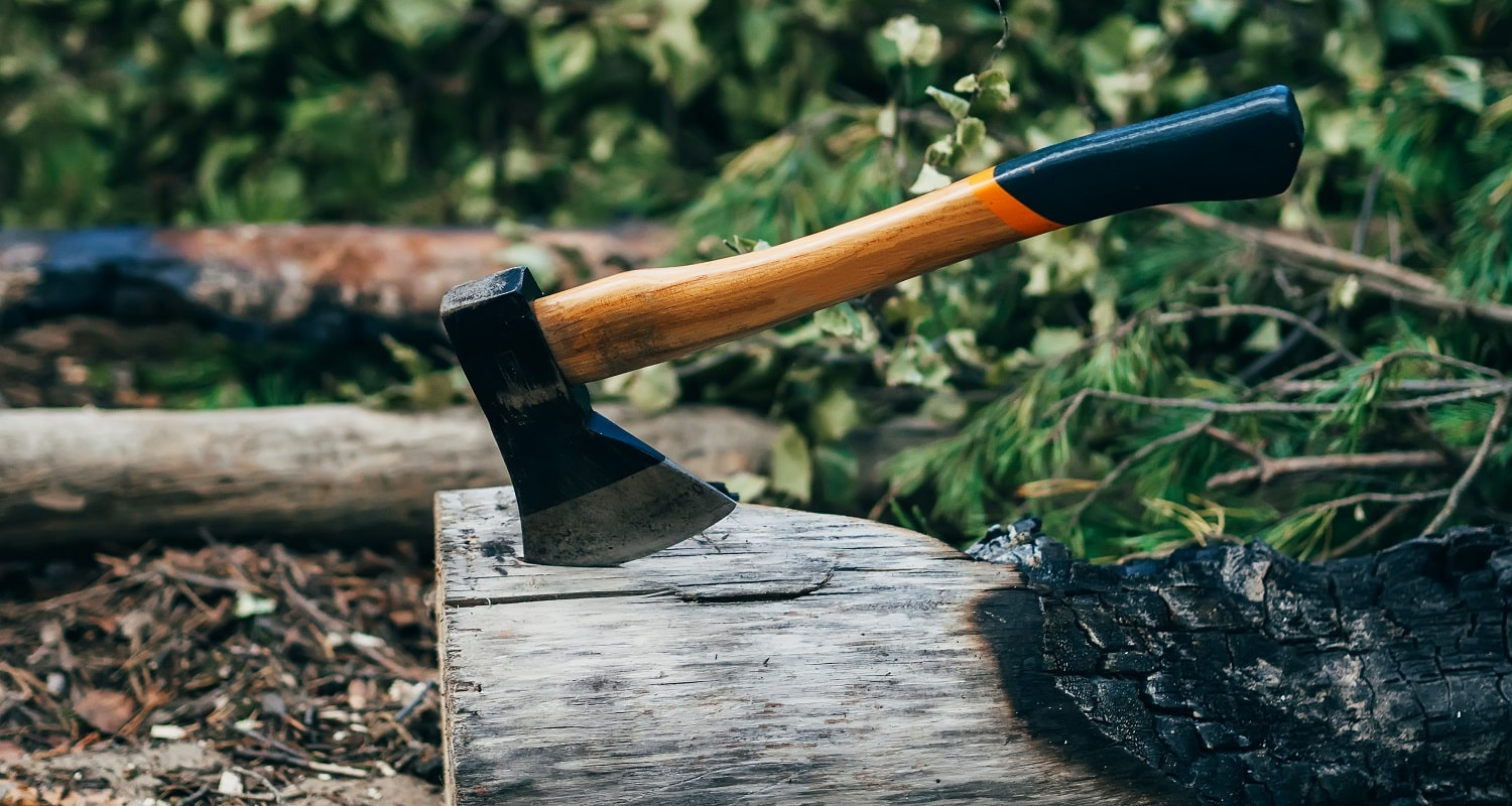 axe stuck in wood log fire pit on a summer vacation in the woods