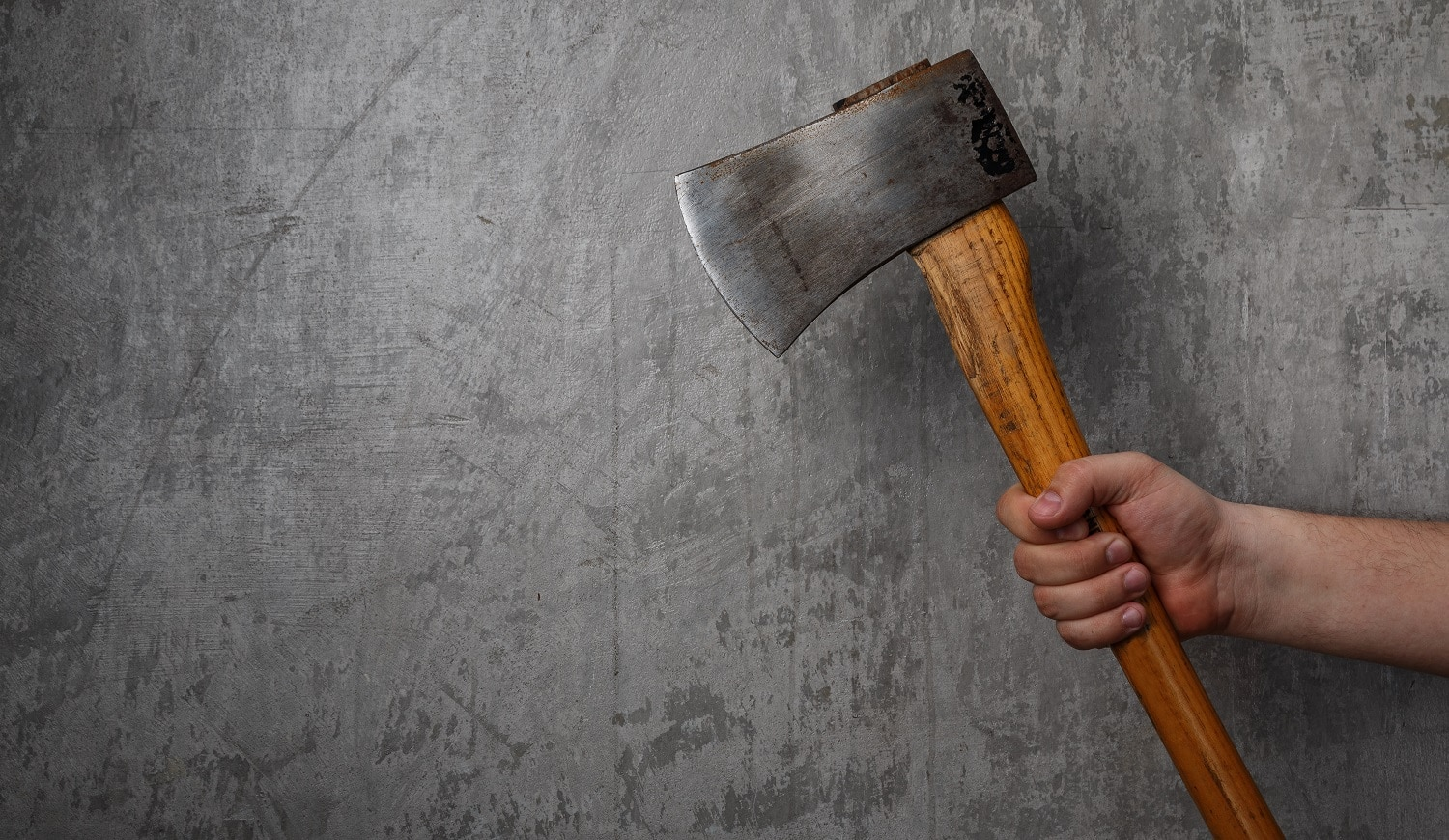 Axe in male hand over old dirty wall