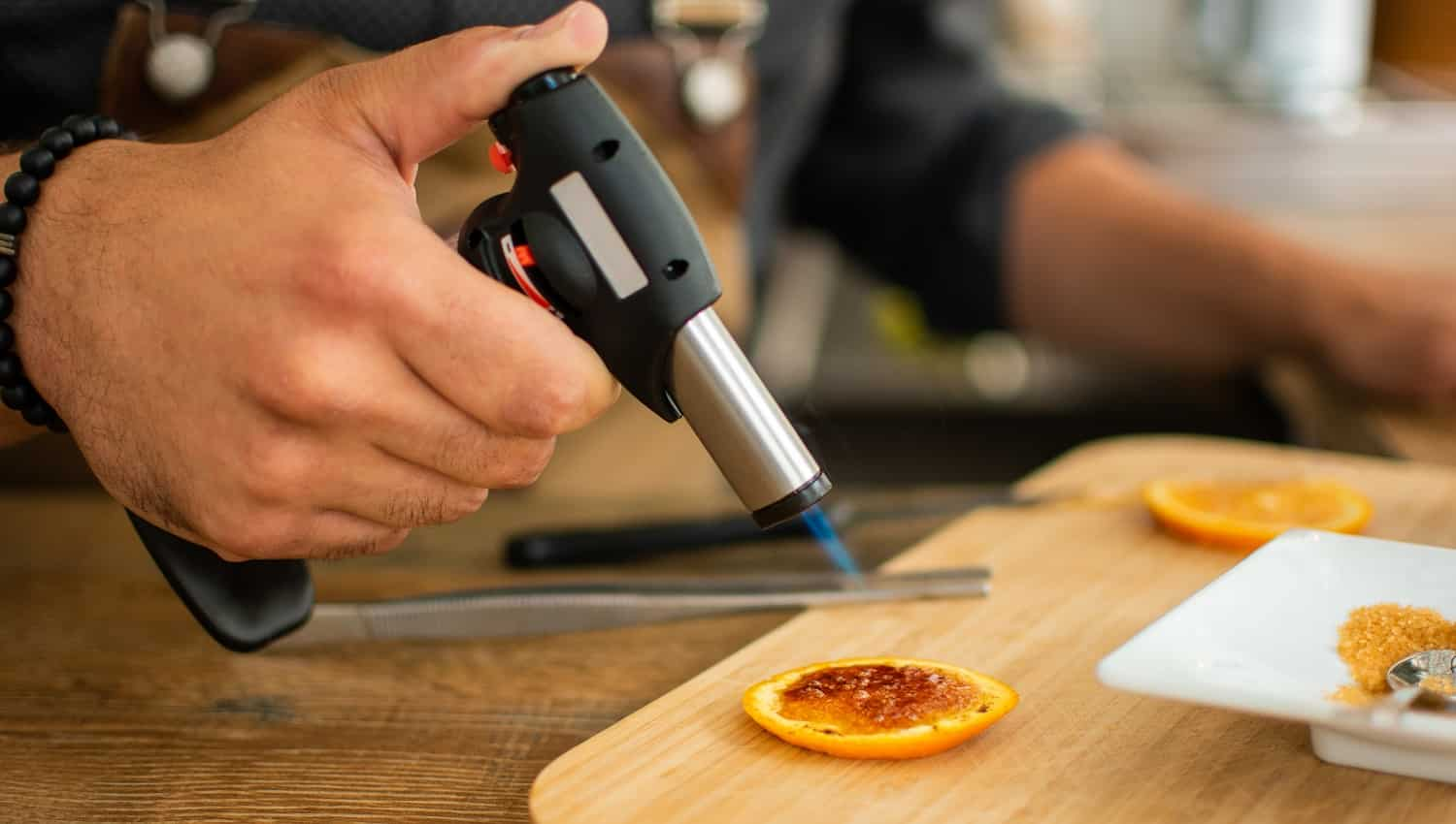 Barman burns orange with gas torch in bar for preparing cocktail. Profession concept.