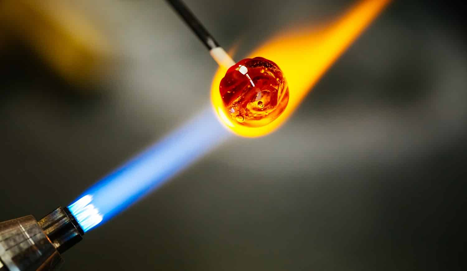 Close-up of glass bead melting in gas-burner fire, craftwork