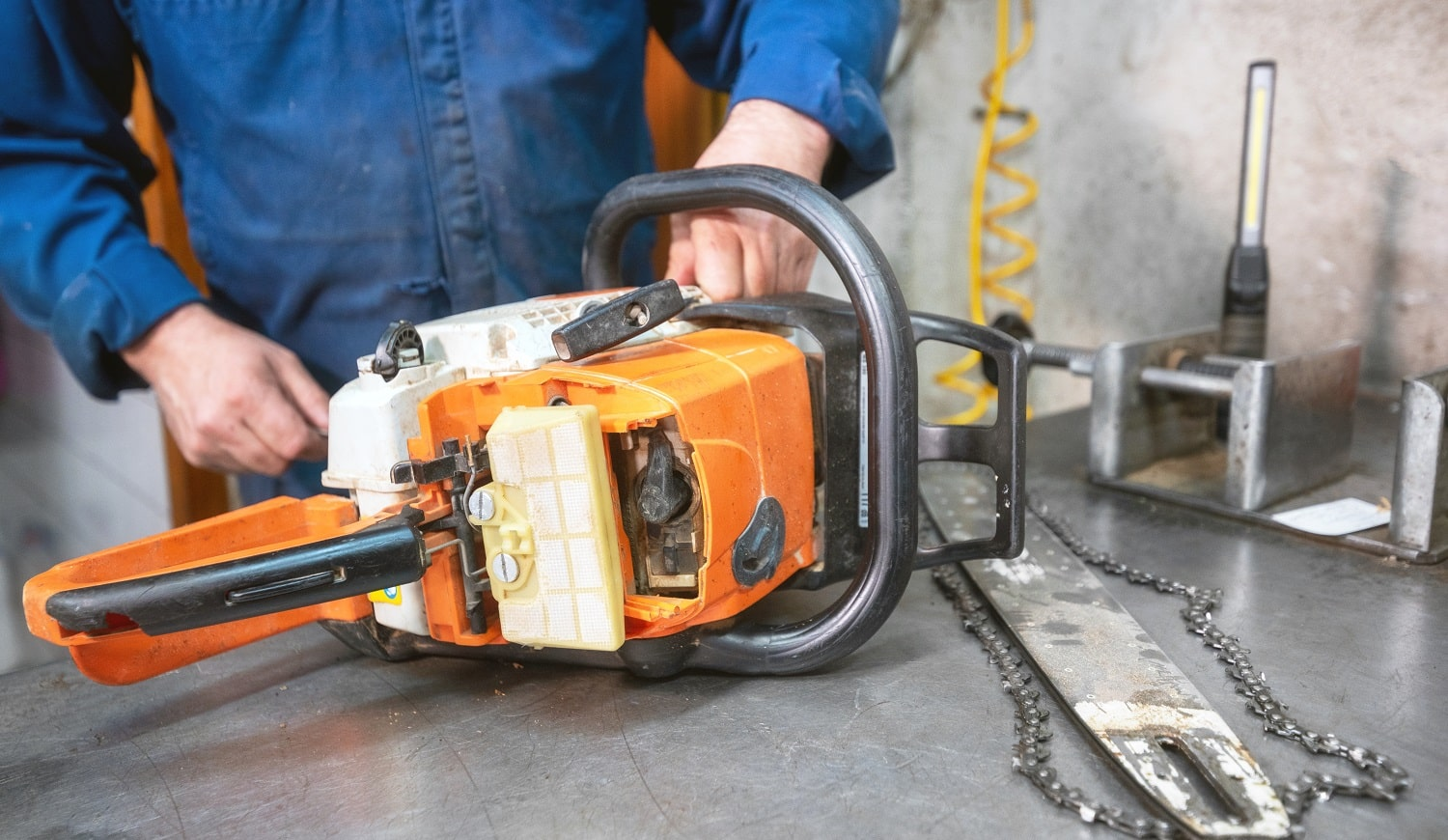 Mechanic repairing a chainsaw. Man repairing a chainsaw in workbench .