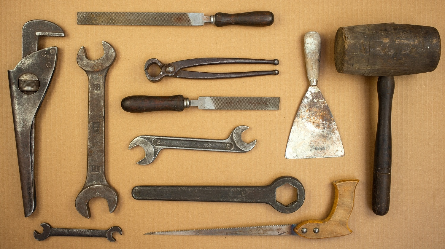 View of old set tools. Hammer, putty, knife, pliers, saw, file, wrench