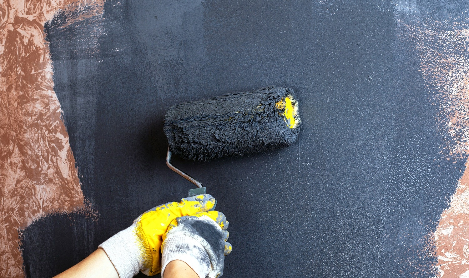 hand paint the walls with a roller gray color. apartment repair concept.