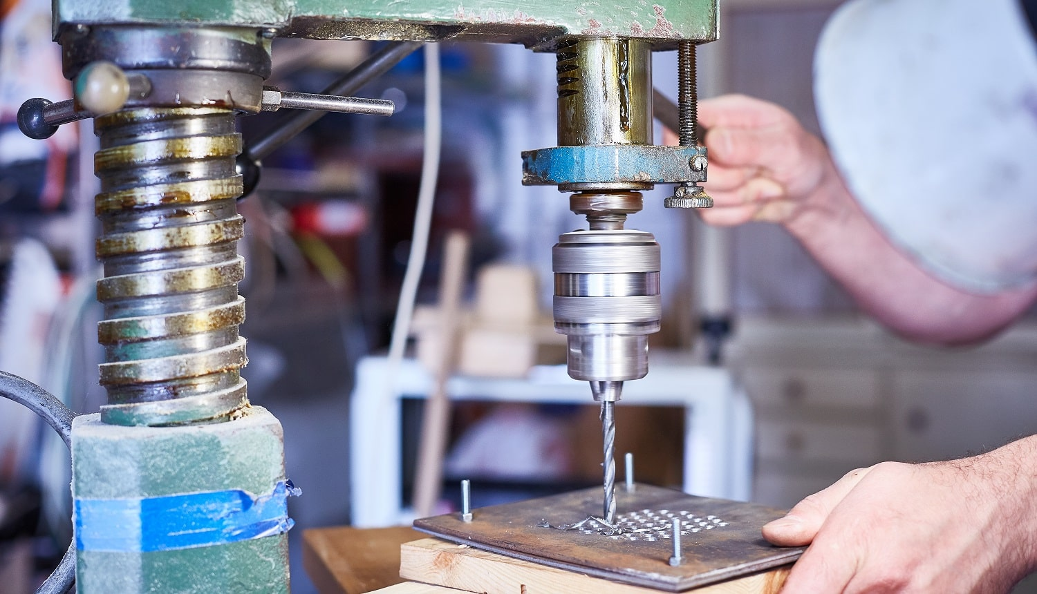 Close-up. hand heavy industrial worker is working on metal work factory process by performing mechanical turning operation at machine for steel structure industry.