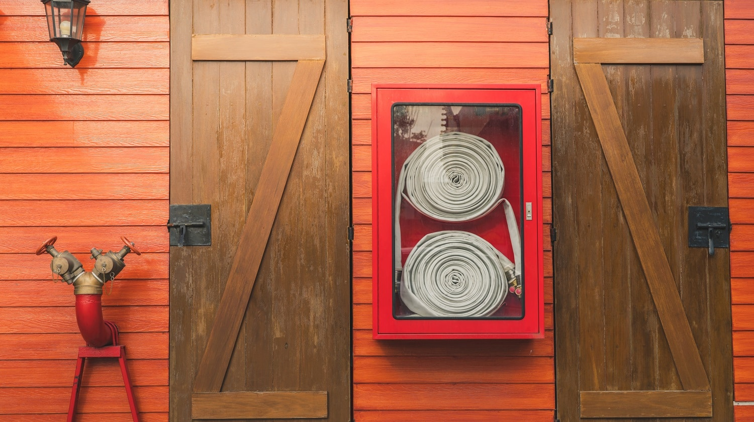 Fire hose in red cabinet hanging on orange wooden wall. Fire emergency equipment box for safety and security system. Fire safety pump. Deluge system of firefighting system. Plumbing fire protection.