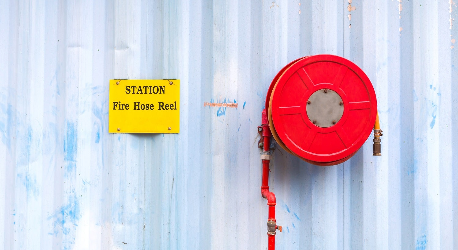 fire hose reel in metal wall industrail image