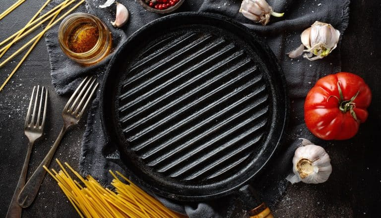 Italian food background with ingredients for cooking and grill pan on dark table.