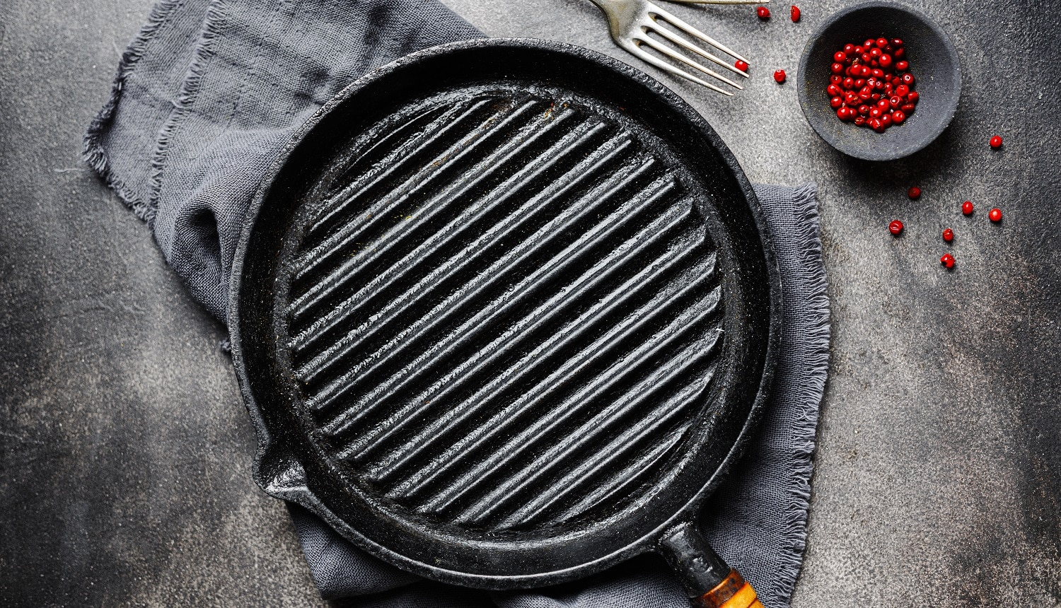 Empty old iron grill pan with napkin on dark background. Cooking concept.