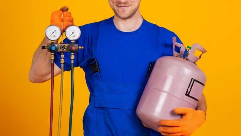 Young cheerful smiling air conditioning specialist. Repair of air conditioners and manometers, measuring equipment for refueling air conditioners. On a yellow background