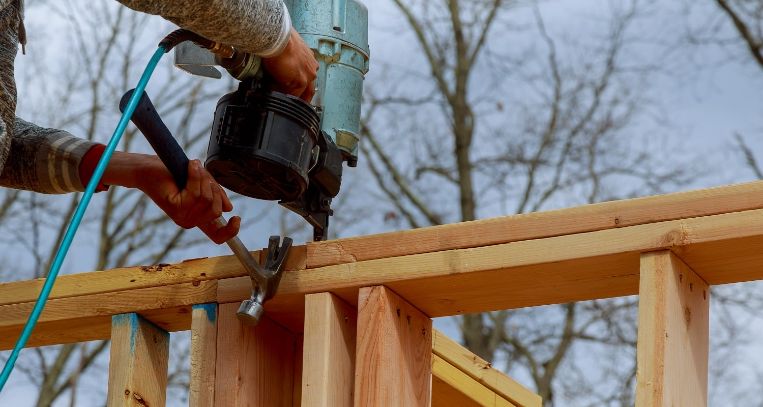Authentic construction worker framing building contractor using nail gun