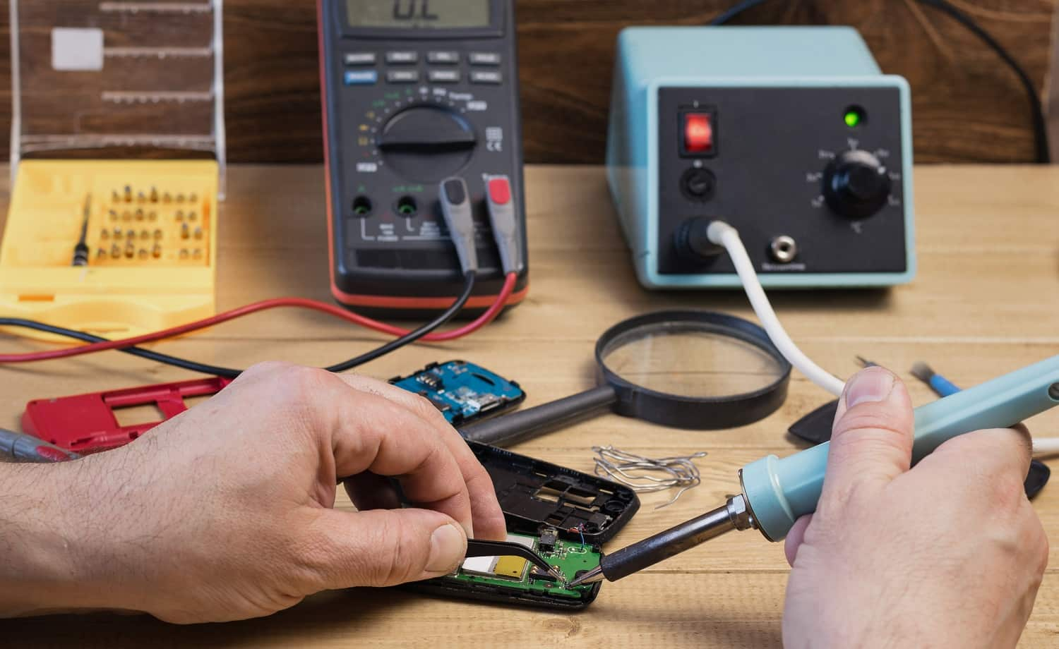 Man repairing mobile phone with a soldering iron. The concept of mobile phone repair.