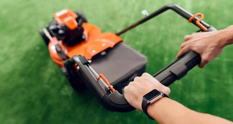 A man holds a lawn mower for the handle.