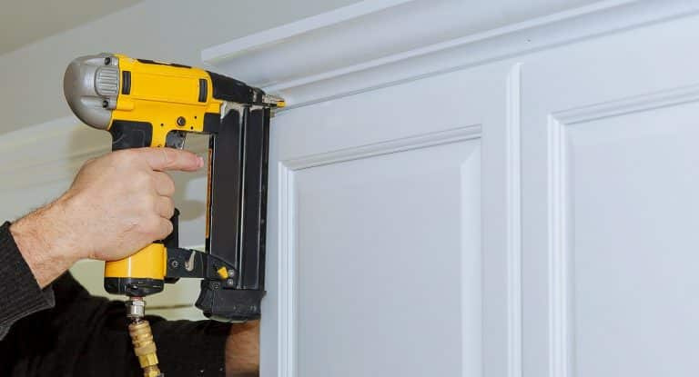 Handyman working using brad nail air gun to Crown Moulding on white kitchen wall cabinets framing trim, with the all power tools