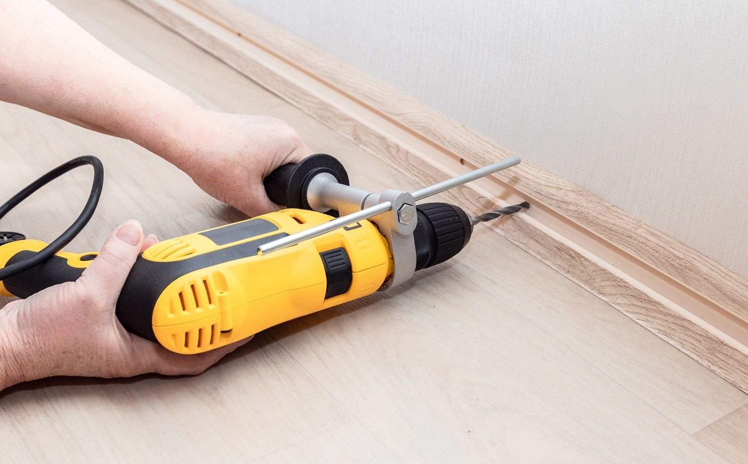 Female hands hold a heavy drill tool and make a hole in the wall for attaching the baseboard. Home repairs. Feminism