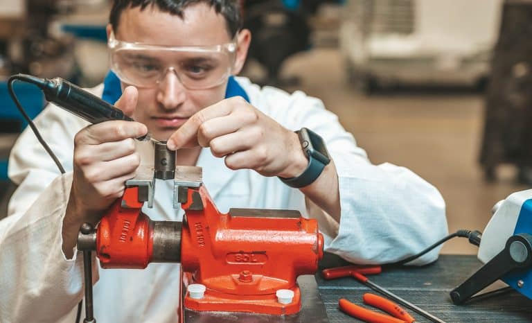 student of technical school on practical exam when working with vise and electric grinder.