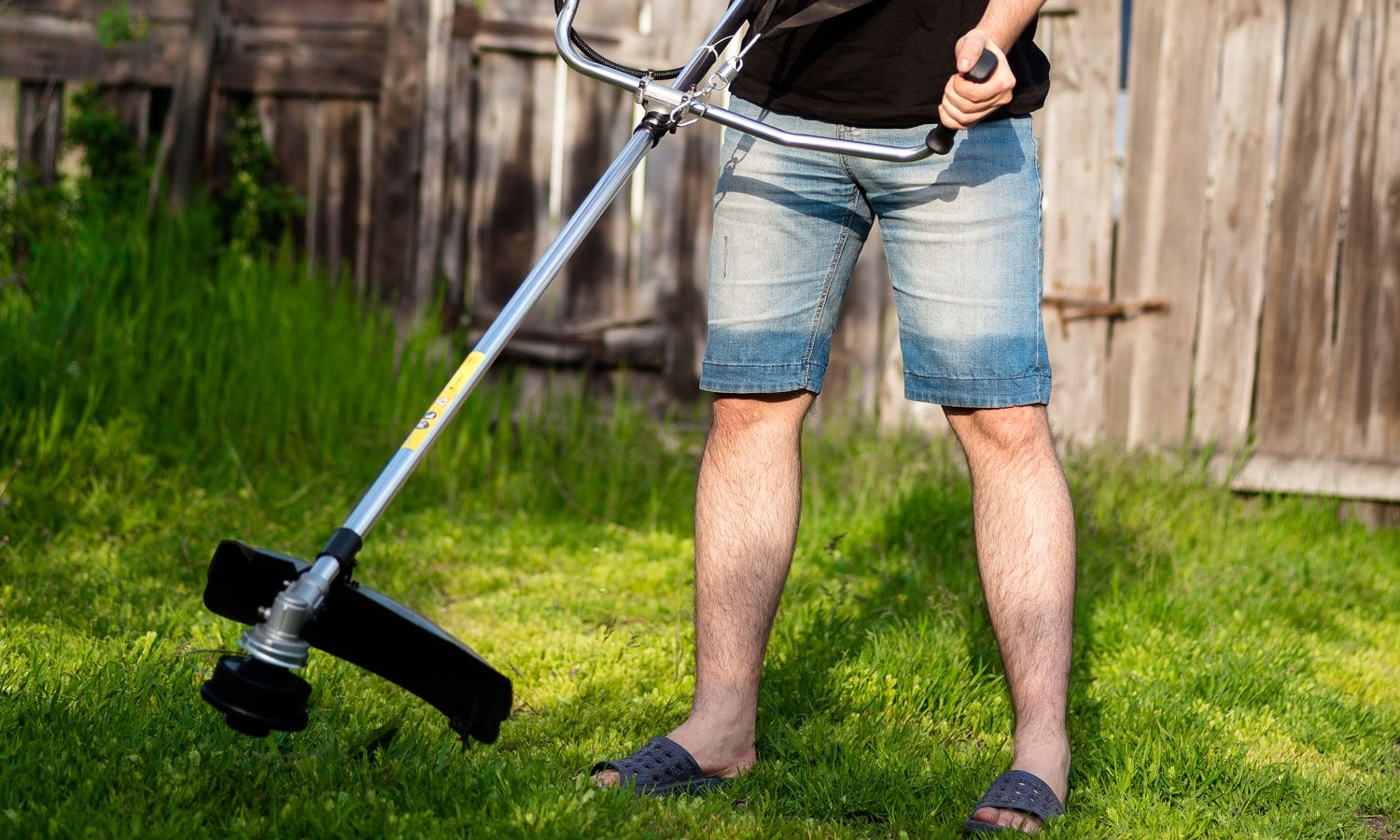 young man in shorts with a professional brush cutter mowing grass in the yard. green lawn, old fence as a background. sunny spring weather.