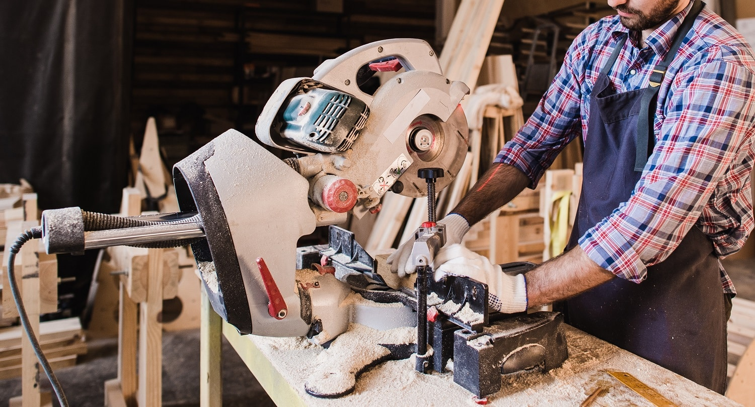 Carpenter Using Circular Saw for wood at his workshop.