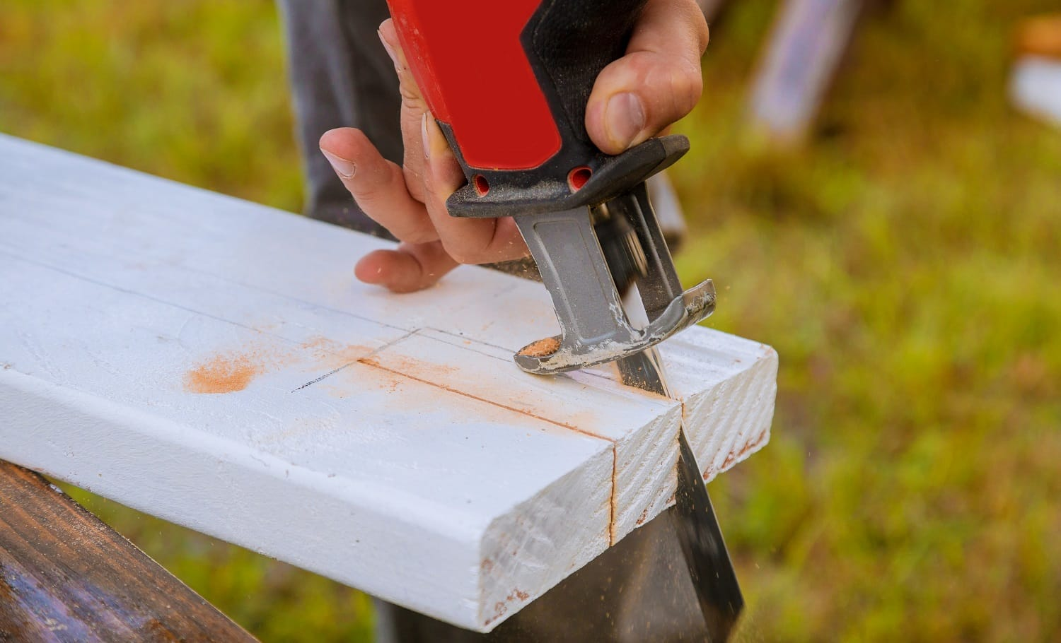 A man is cutting a board of wood with jigsaw detail of a cutting wooden board with saw dust.