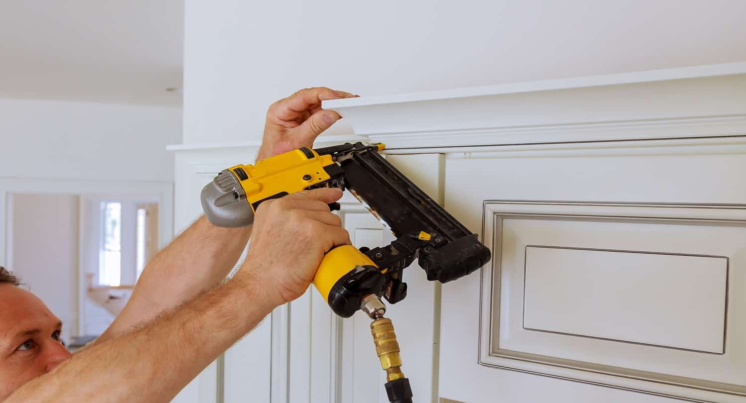Carpenter brad using nail gun to Crown Moulding on kitchen cabinets framing trim, with the warning label that all power tools have on them shown illustrating safety concept