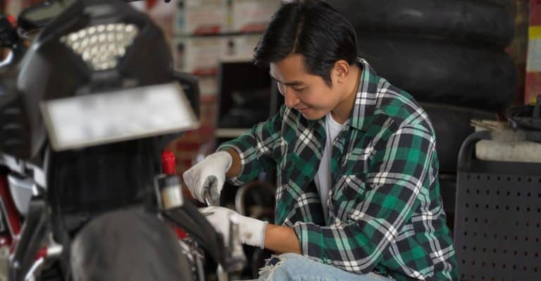 Cropped view of motorcycle mechanic using a wrench and socket on a motorcycle