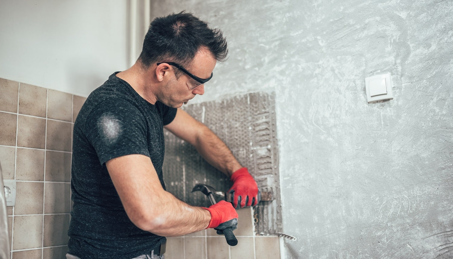 Man wearing red safety gloves removing wall tails in the kitchen