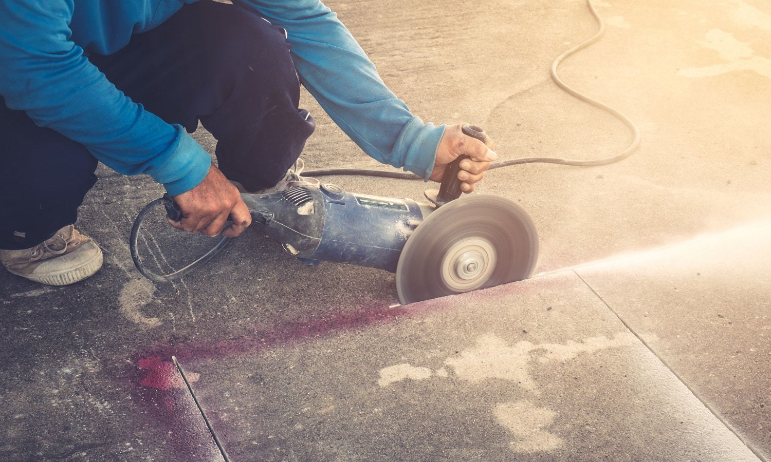 Close up hand man cutting concrete floor with machine.