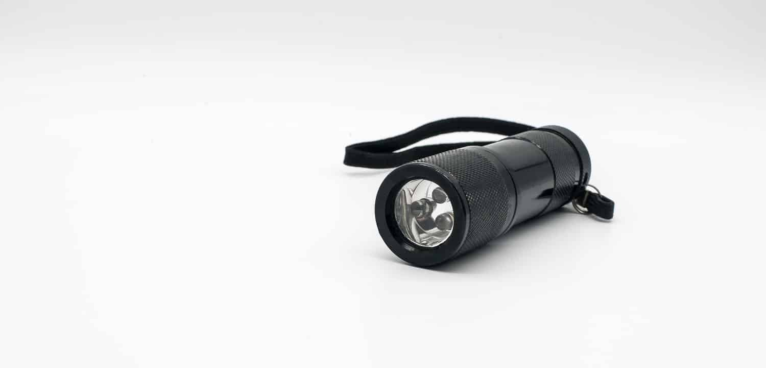 LED black metal flashlight isolated on white background