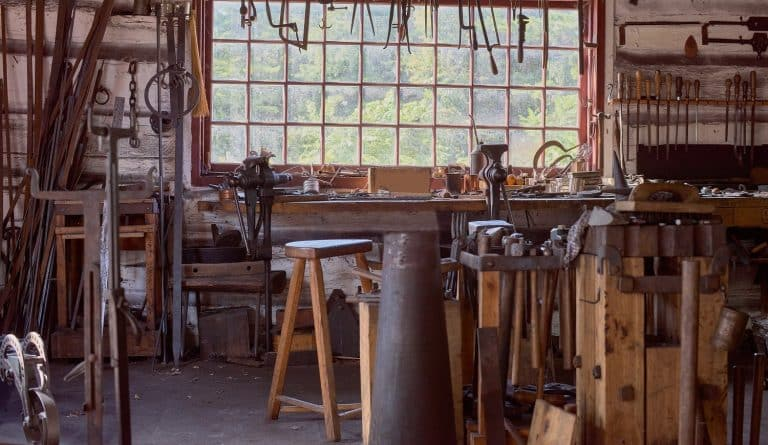 large table by the window Old vintage craftsman's workshop blacksmith with a jaw vise and other tools.
