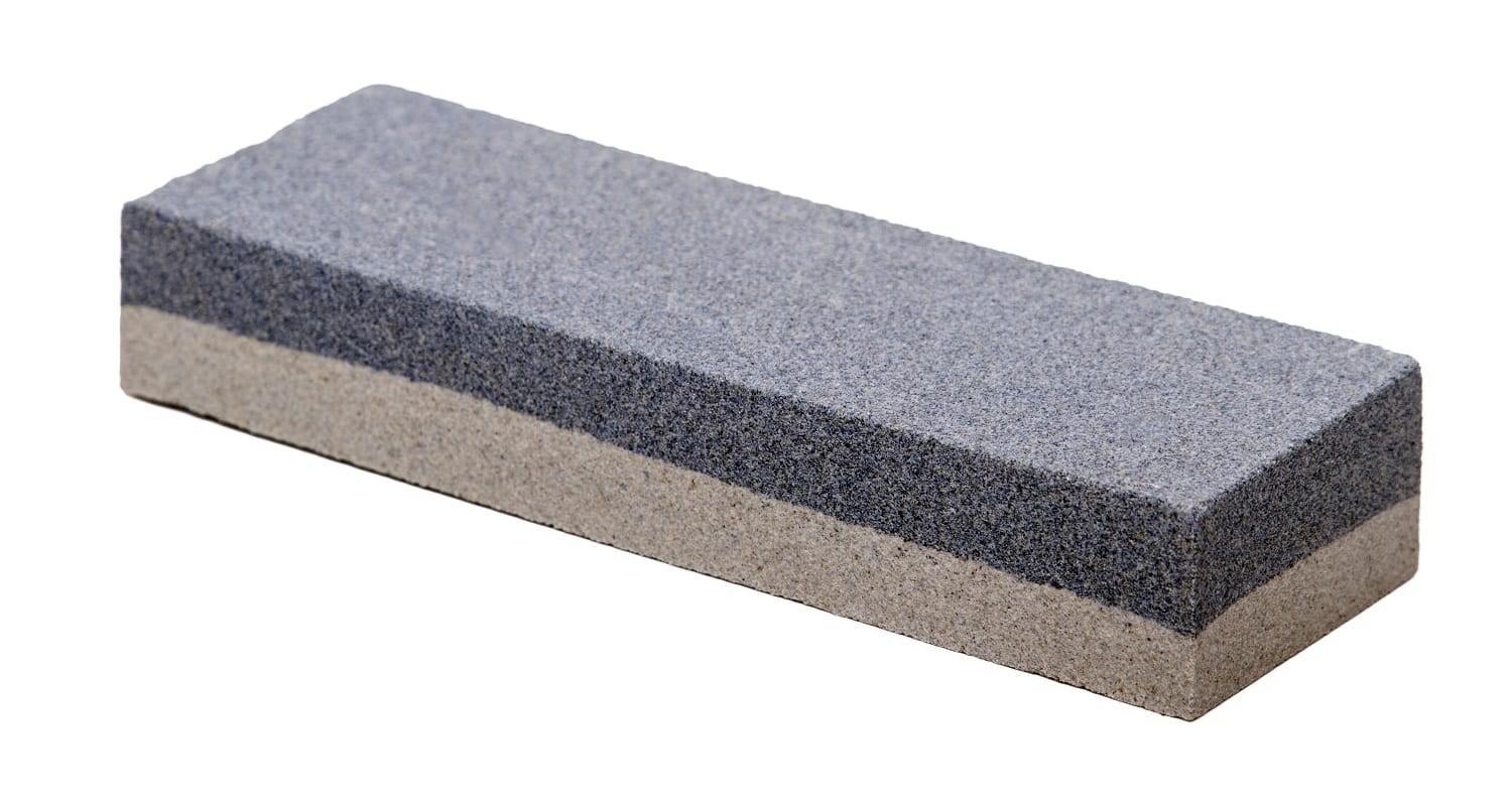 Close up view of an abrasive whetstone isolated on a white background.