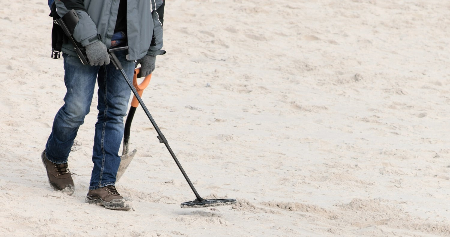 A man with a metal detector is looking for jewels.