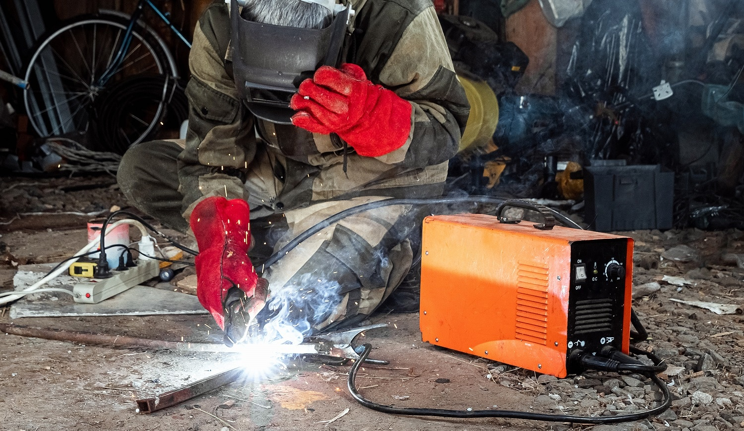 A male welder in a welding mask works with an arc electrode in his garage. Welding, construction, metal work
